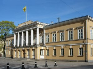 Image shows the grand two storey building main building at Åbo Akademi. It is built in a neo-classical style with fix pillars above the central entrance,and faces onto a cobbled road.