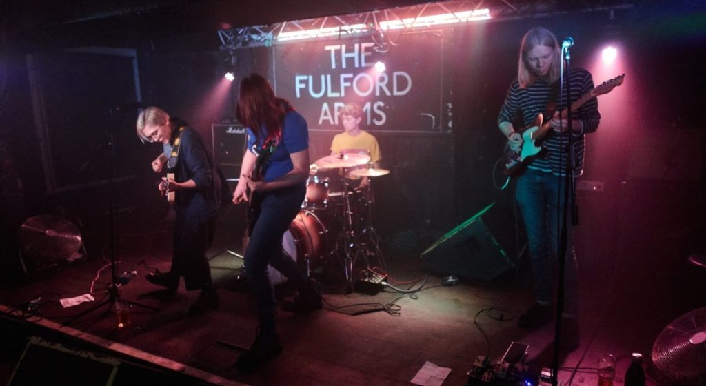 Photograph of four people playing rock music enthusiastically.